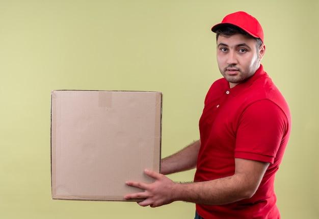 Junger lieferbote in der roten uniform und in der kappe, die karton mit sicherem ausdruck über grüner wand hält