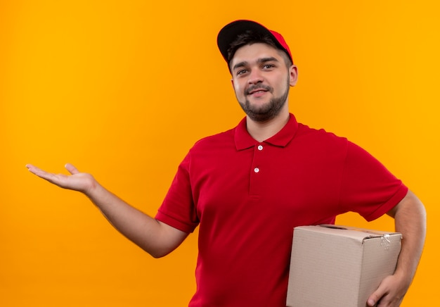 Junger lieferbote in der roten uniform und in der kappe, die kastenpaket darstellt, das mit arm des handkopienraums lächelnd präsentiert