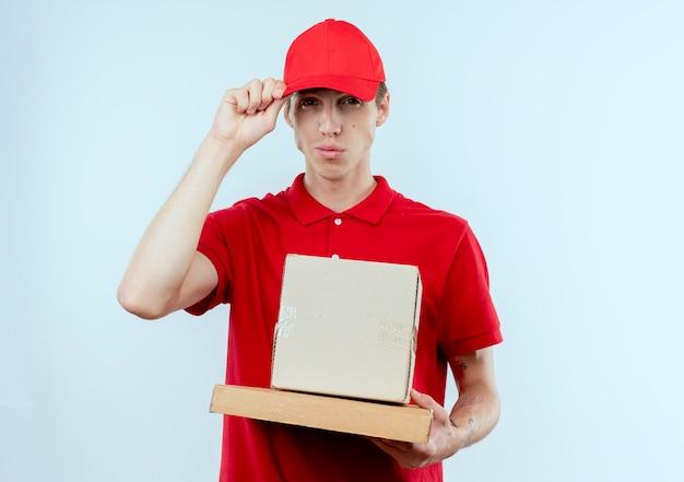 Junger lieferbote in der roten uniform und in der kappe, die kastenpaket und in der pizzaschachtel hält und zuversichtlich schaut, seine kappe stehend über weißer wand berührt