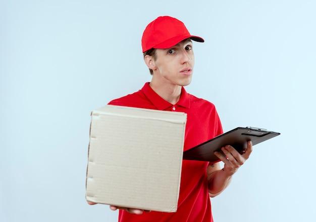 Junger lieferbote in der roten uniform und in der kappe, die kastenpaket und zwischenablage hält, die nach vorne verwirrt über weißer wand stehen