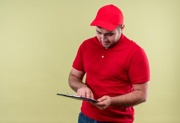 Junger lieferbote in der roten uniform und in der kappe, die klemmbrett mit lächeln auf gesicht betrachtet, das über grüner wand steht