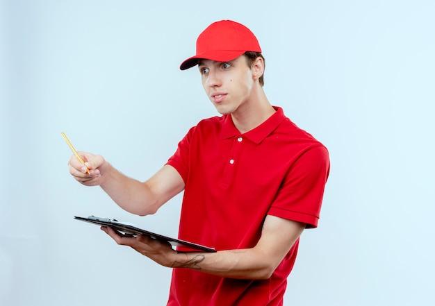 Junger lieferbote in der roten uniform und in der kappe, die klemmbrett und bleistift halten, die beiseite mit lächeln auf gesicht stehen, das über weißer wand steht