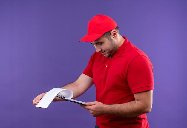 Junger lieferbote in der roten uniform und in der kappe, die leere seiten in der zwischenablage lächelnd souverän stehend über lila wand betrachten