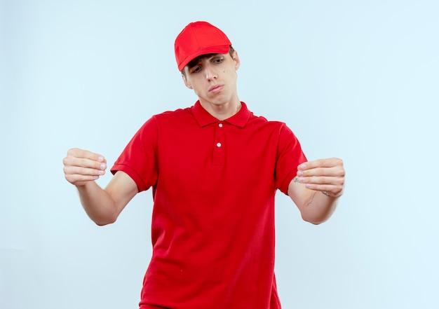 Junger lieferbote in der roten uniform und in der kappe, die mit traurigem ausdruck auf gesicht gestikulierend mit händen, körpersprachenkonzept stehen über weißer wand suchen