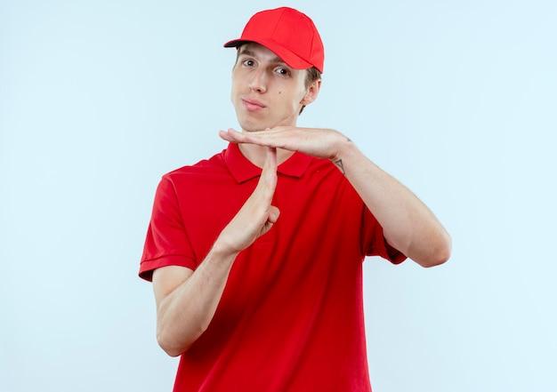 Junger lieferbote in der roten uniform und in der kappe, die nach vorne mit ernstem gesicht schauen, das auszeitgeste mit händen macht, die über weißer wand stehen