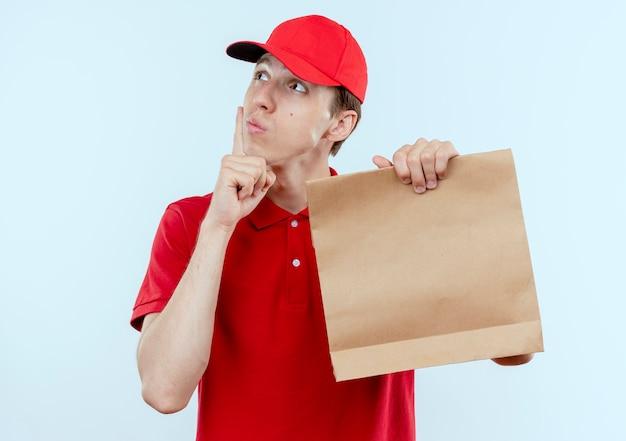 Junger lieferbote in der roten uniform und in der kappe, die papierpaket hält, das mit nachdenklichem ausdruck beiseite steht, der über weißer wand steht