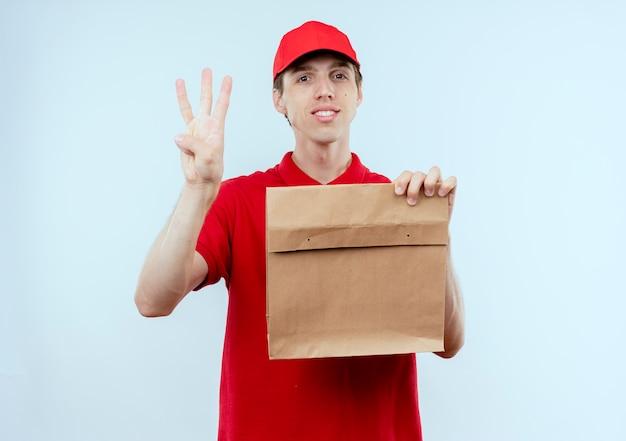 Junger lieferbote in der roten uniform und in der kappe, die papierpaket hält, das nummer drei zeigt, das zuversichtlich steht, über weißer wand zu stehen