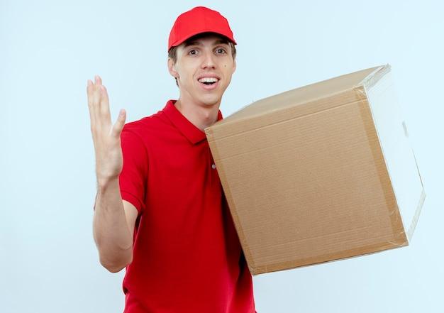 Junger lieferbote in der roten uniform und in der kappe, die pappkarton hält, der mit arm heraus nach vorne schaut, als mit lächeln auf gesicht fragend über weißer wand fragt