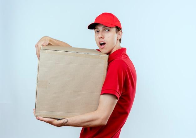 Junger lieferbote in der roten uniform und in der kappe, die pappkarton hält, der nach vorne überrascht und erstaunt über weißer wand steht