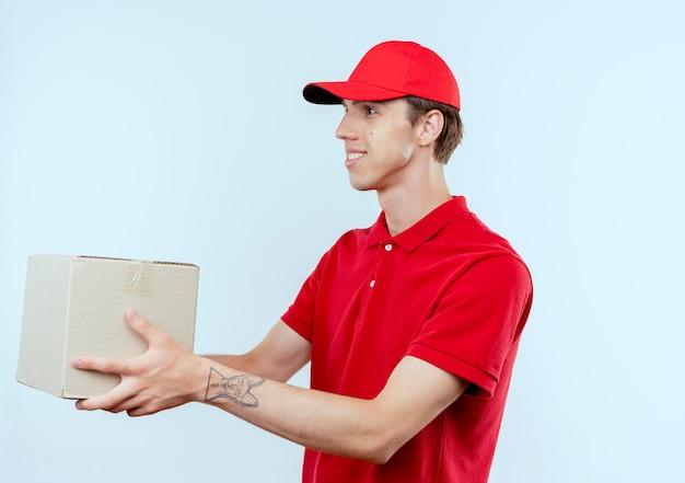Junger lieferbote in der roten uniform und in der kappe, die pappkarton zu einem lächelnden kunden über weißer wand geben