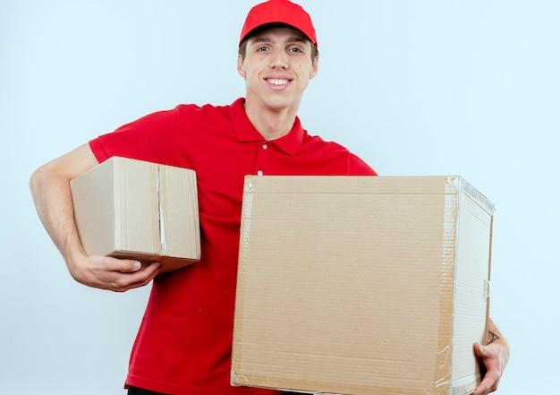 Junger lieferbote in der roten uniform und in der kappe, die pappkartons hält, die nach vorne lächelnd zuversichtlich über weiße wand stehen