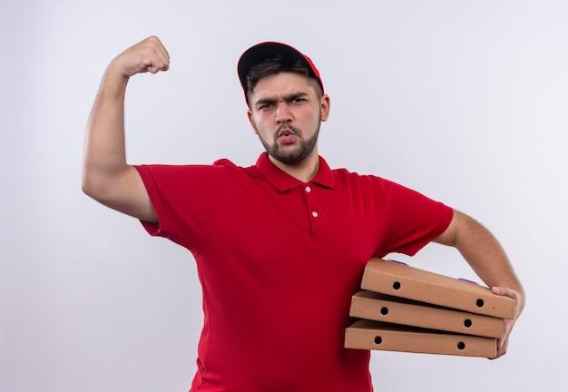 Junger lieferbote in der roten uniform und in der kappe, die pizzakästen hält, die faust erhöhen, die bizeps mit ernstem gesicht, gewinnerkonzept zeigt