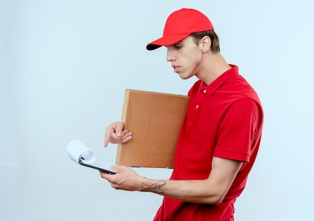 Junger lieferbote in der roten uniform und in der kappe, die pizzaschachtel und zwischenablage hält, die es mit ernstem gesicht betrachten, das über weißer wand steht