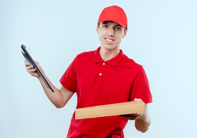Junger lieferbote in der roten uniform und in der kappe, die pizzaschachtel und zwischenablage hält, die zuversichtlich stehen über weißer wand stehen