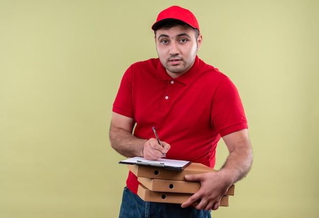 Junger lieferbote in der roten uniform und in der kappe, die pizzaschachteln hält, die auf leerer seite freundlich lächelnd über grüner wand stehen