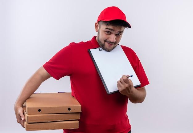 Junger lieferbote in der roten uniform und in der kappe, die pizzaschachteln hält, die zwischenablage mit leeren seiten zeigen und um unterschrift bitten