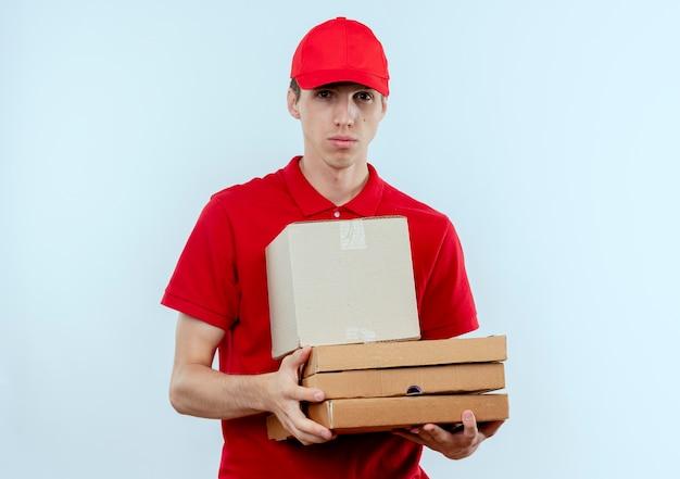 Junger lieferbote in der roten uniform und in der kappe, die pizzaschachteln halten, die nach vorne mit ernstem gesicht stehen, das über weißer wand steht
