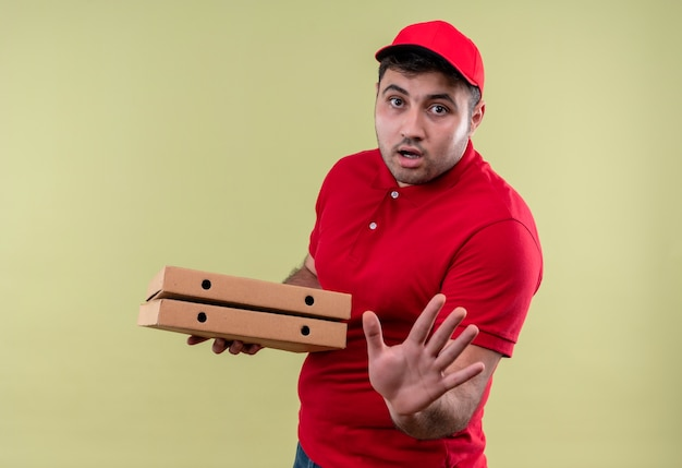 Junger lieferbote in der roten uniform und in der kappe, die pizzaschachteln halten stoppschild mit hand mit angstausdruck stehen über grüner wand halten