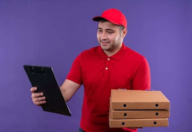 Junger lieferbote in der roten uniform und in der kappe, die pizzaschachteln und zwischenablage lächelnd mit glücklichem gesicht über lila wand stehen