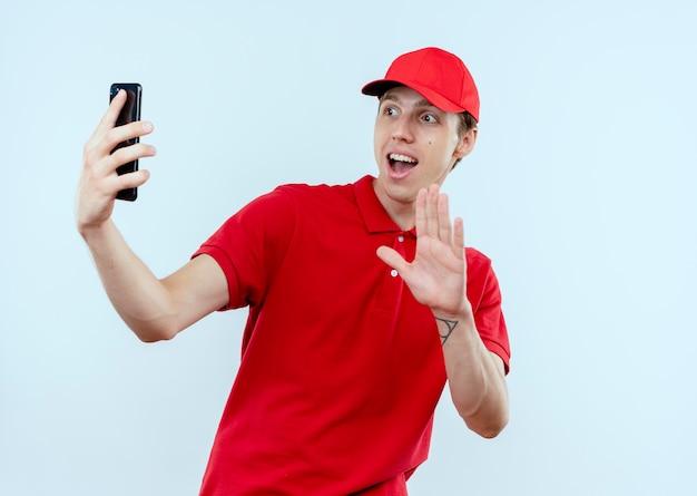Junger lieferbote in der roten uniform und in der kappe, die smartphone hält, das das lächelnde selfie winkend mit einer hand hält, die über weißer wand steht