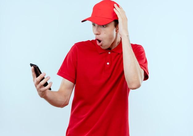 Junger lieferbote in der roten uniform und in der kappe, die smartphone hält, das überrascht und verwirrt mit hand auf seinem kopf für fehler steht, der über weißer wand steht