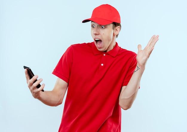 Junger lieferbote in der roten uniform und in der kappe, die smartphone halten, das überrascht und verwirrt mit erhöhtem arm steht, der über weißer wand steht