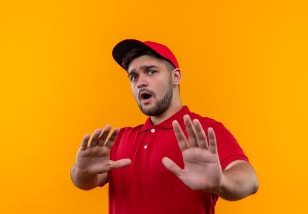 Junger lieferbote in der roten uniform und in der kappe, die stoppschild mit besorgten und verängstigten händen machen