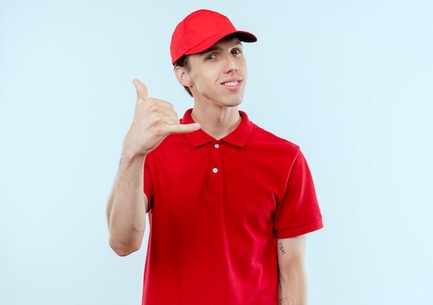 Junger lieferbote in der roten uniform und in der kappe, die zuversichtlich lächeln, rufen mich geste stehend über weiße wand