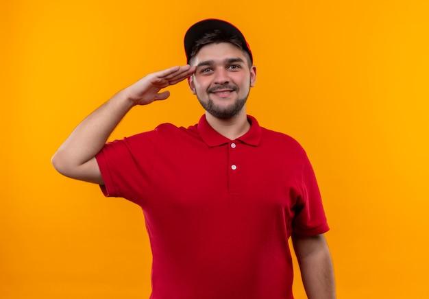 Junger lieferbote in der roten uniform und in der kappe, die zuversichtlich salutierend suchen