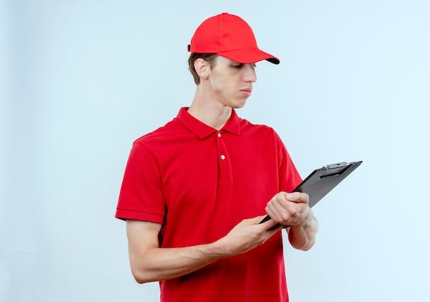 Junger lieferbote in der roten uniform und in der kappe, die zwischenablage hält, die es mit ernstem gesicht betrachtet, das über weißer wand steht
