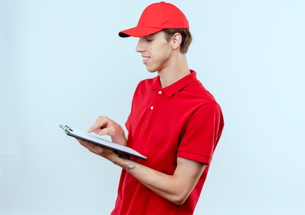 Junger lieferbote in der roten uniform und in der kappe, die zwischenablage hält, die es mit lächeln auf gesicht betrachtet, das über weißer wand steht