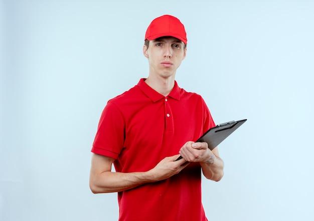 Junger lieferbote in der roten uniform und in der kappe, die zwischenablage hält, schaut nach vorne mit ernstem gesicht, das über weißer wand steht