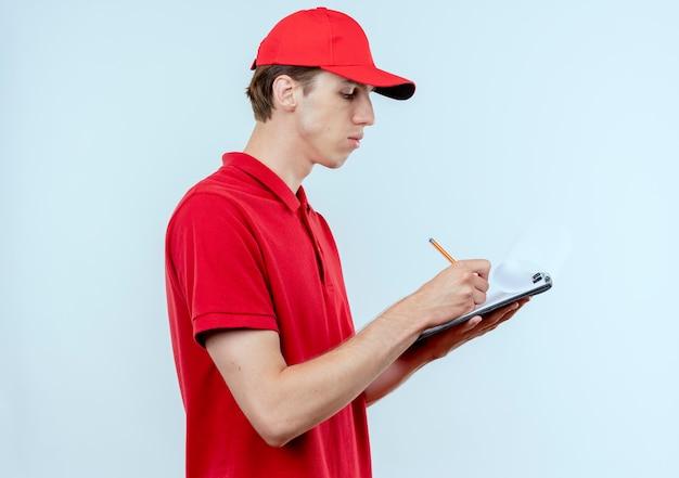 Junger lieferbote in der roten uniform und in der kappe, die zwischenablage hält, schreibt etwas mit ernstem gesicht, das über weißer wand 2 steht