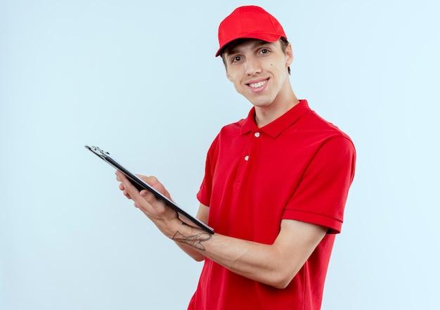 Junger lieferbote in der roten uniform und in der kappe, die zwischenablage mit leeren seiten hält, die nach vorne lächelnd zuversichtlich über weißer wand stehen