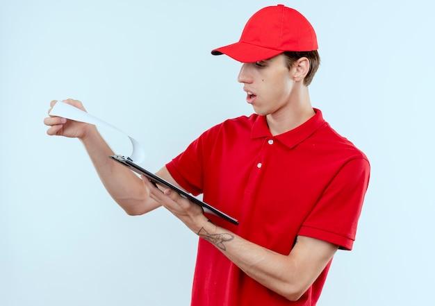 Junger lieferbote in der roten uniform und in der kappe, die zwischenablage mit leeren seiten hält, die überrascht stehen über weißer wand stehen