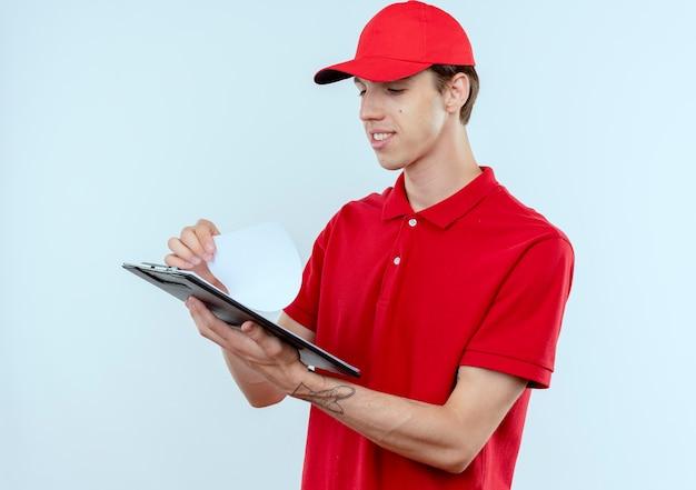 Junger lieferbote in der roten uniform und in der kappe, die zwischenablage mit leeren seiten hält, die zuversichtlich stehen, über weißer wand stehen