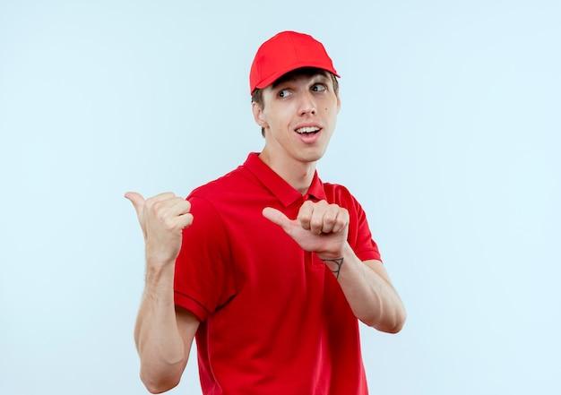 Junger lieferbote in der roten uniform und in der kappe glücklich und positiv, die mit den daumen über der weißen wand zurückweisend zeigen