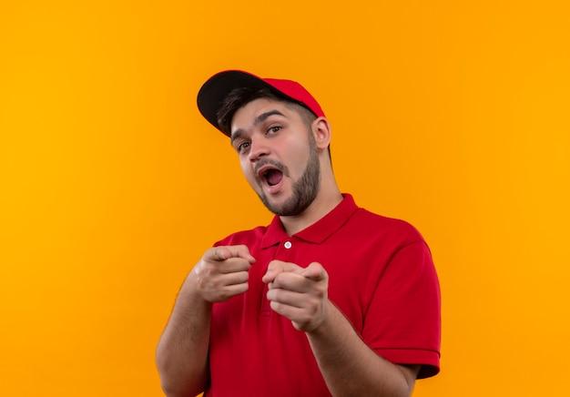 Junger lieferbote in der roten uniform und in der kappe glücklich und positiv, die mit den fingern zur kamera zeigen