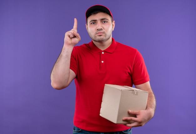 Junger lieferbote in der roten uniform und in der kappenhaltebox, die oben mit zeigefinger mit ernstem gesicht über lila wand stehen zeigt