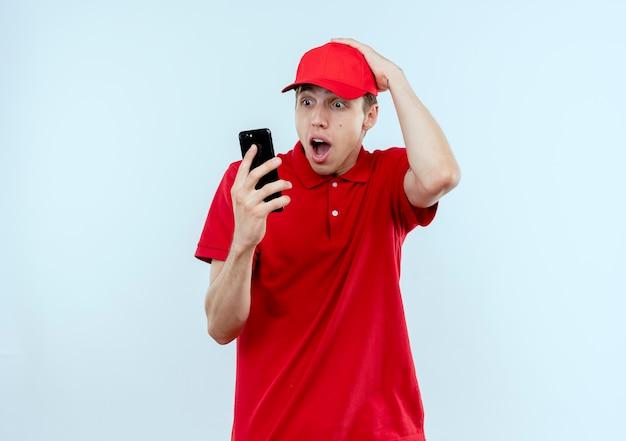 Junger lieferbote in der roten uniform und in der mütze, die den bildschirm seines handys betrachten, überrascht und verwirrt mit der hand auf seinem kopf, der über weißer wand steht