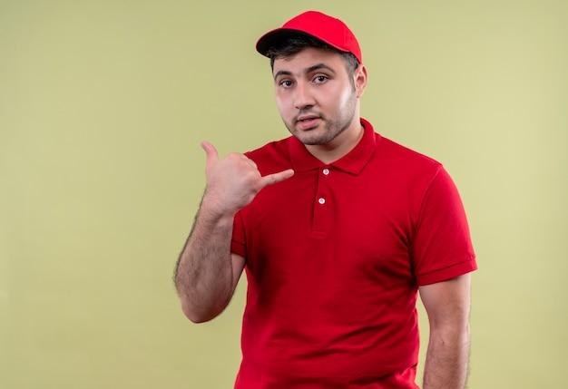 Junger lieferbote in der roten uniform und in der mütze, die mich geste anlächelt, die zuversichtlich über grüner wand stehend lächelt