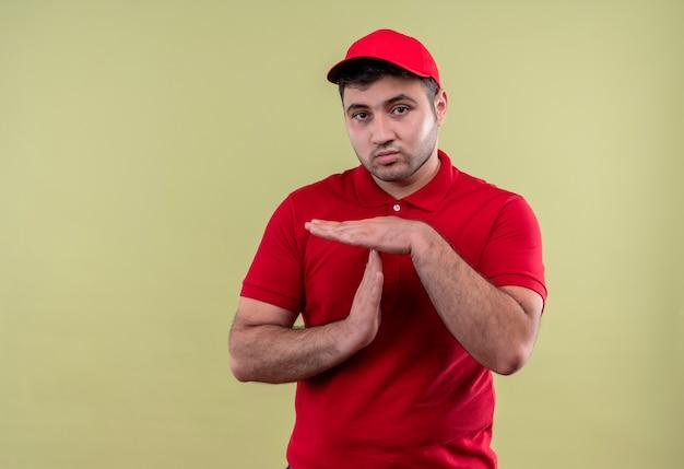 Junger lieferbote in der roten uniform und in der mütze, die müde schauen, auszeitgeste mit den händen stehend über grüner wand machen