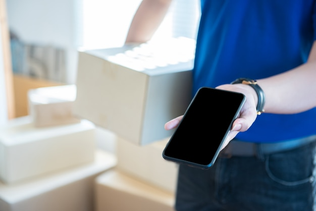 Junger lieferbote in der uniform, die smartphone mit leerem bildschirm hält und zeigt. ai transporttechnologiekonzept.