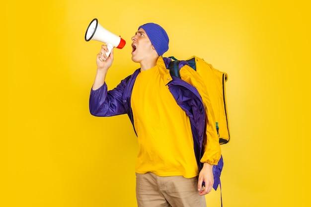 Junger lieferbote in gelber uniform liefert den kunden die vorstellung von bequemlichkeit und geschwindigkeit