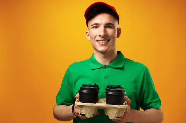 Junger lieferbote in grünem t-shirt und mütze mit gesichtsmaske gegen gelbe oberfläche