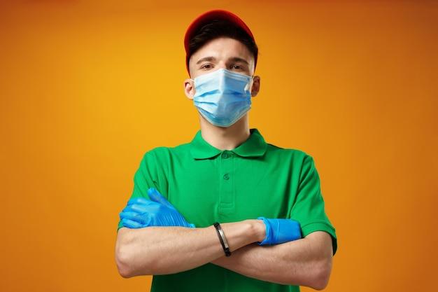 Junger lieferbote in grünem t-shirt und mütze mit gesichtsmaske vor gelbem hintergrund