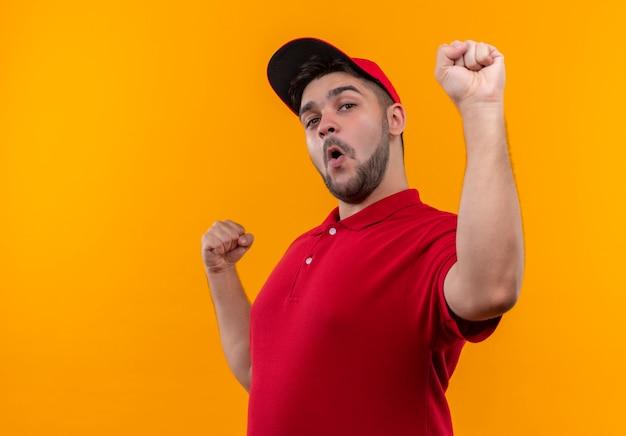Junger lieferbote in roter uniform und geballten mützenfäusten glücklich und aufgeregt
