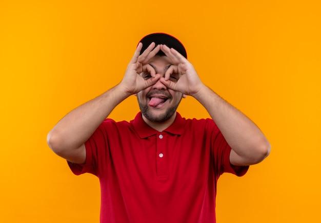 Junger lieferbote in roter uniform und kappe, die ok zeichen mit fingern wie fernglas machen, das durch finger schaut, die zunge herausstrecken