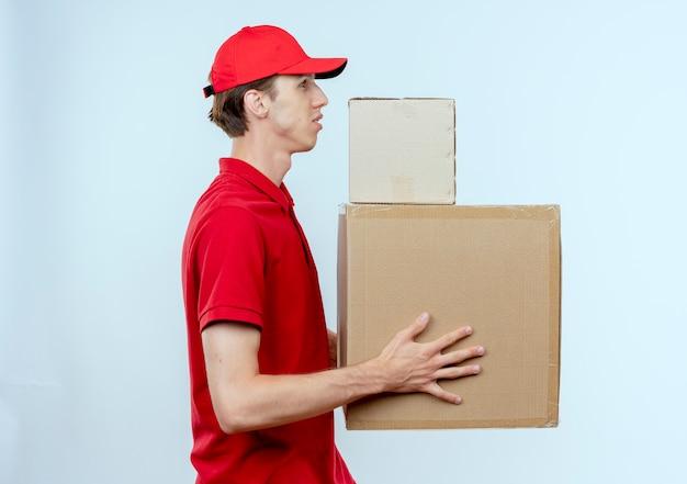 Junger lieferbote in roter uniform und kappe, die pappkartons hält, die seitlich mit ernstem gesicht über weißer wand stehen