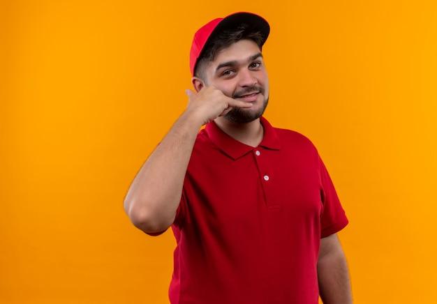 Junger lieferbote in roter uniform und lächelnder mütze der mütze nennen mich geste